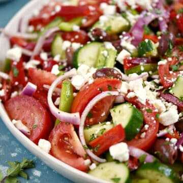 A close-up of tomato wedges, onion, cucumber and bell pepper slices topped with a light vinaigrette and feta cheese in a large white serving platter.