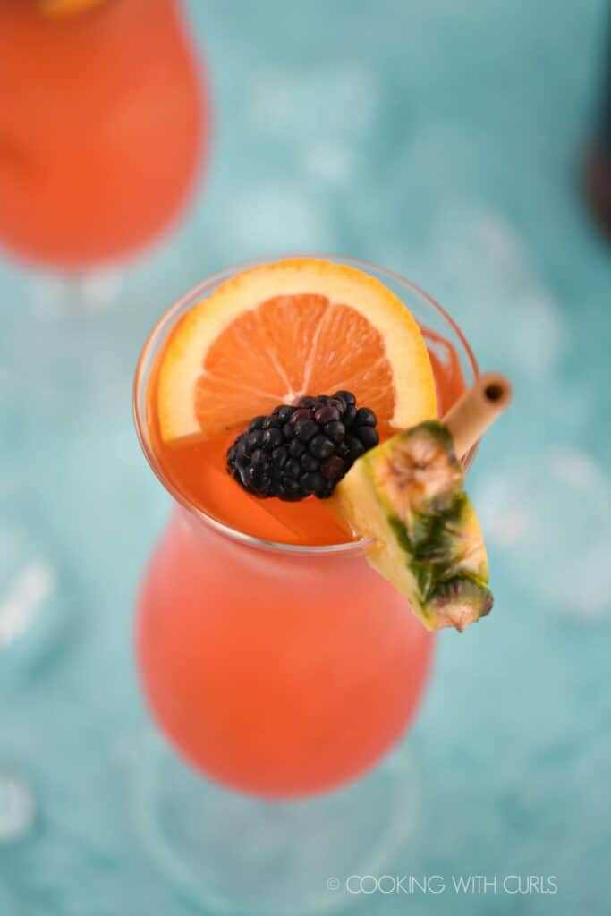 looking down on a pink cocktail garnished with a bamboo straw, pineapple wedge, orange slice and blackberry with a second cocktail in the upper right corner.
