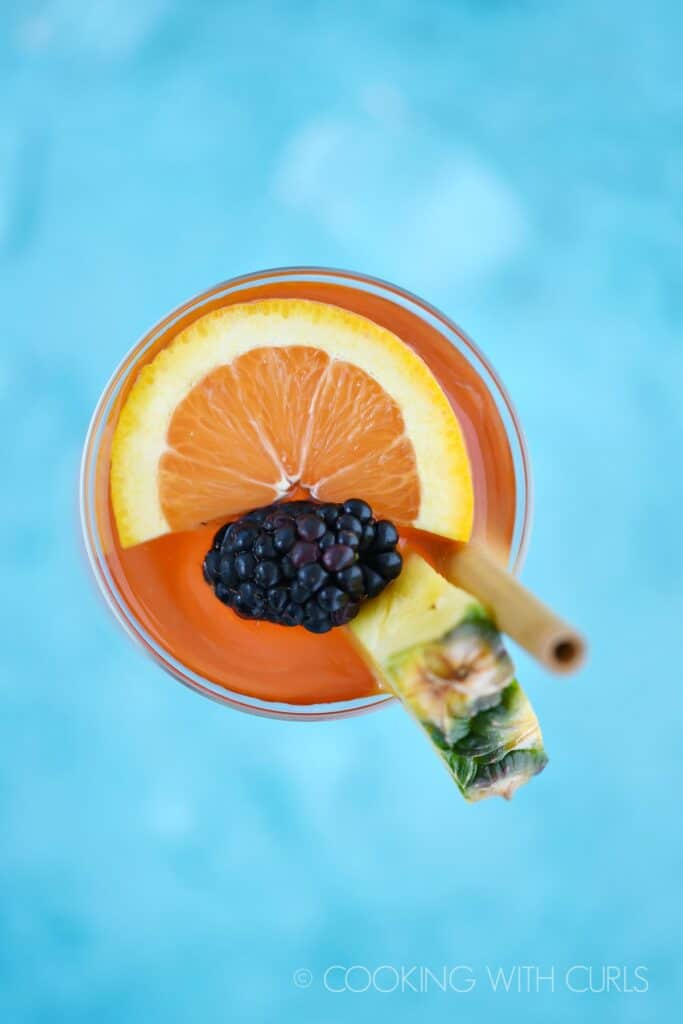 looking directly down on a pink cocktail garnished with a pineapple wedge, orange slice, blackberry and bamboo straw sitting on a bright blue background.