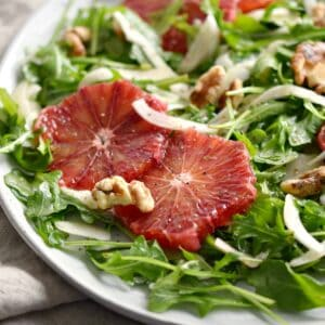 arugula salad with thin slices of fennel and blood oranges on a large white plate.