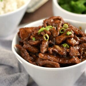 a white bowl filled with mongolian beef with bowls of broccoli and rice in the background.