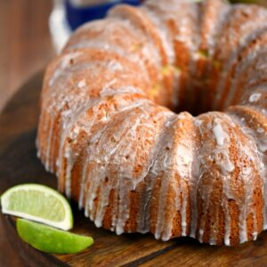 margarita bundt cake on a wood cake platter with lime wedges on the side.