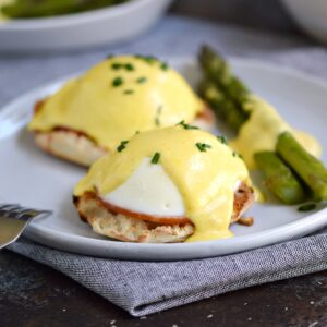 eggs benedict covered in hollandaise with asparagus spears on the side.