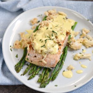 a salmon filet on a bed of asparagus spears topped with crab meat and hollandaise sauce.