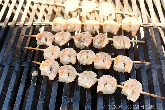 Cooked, skewered shrimp on the grill.