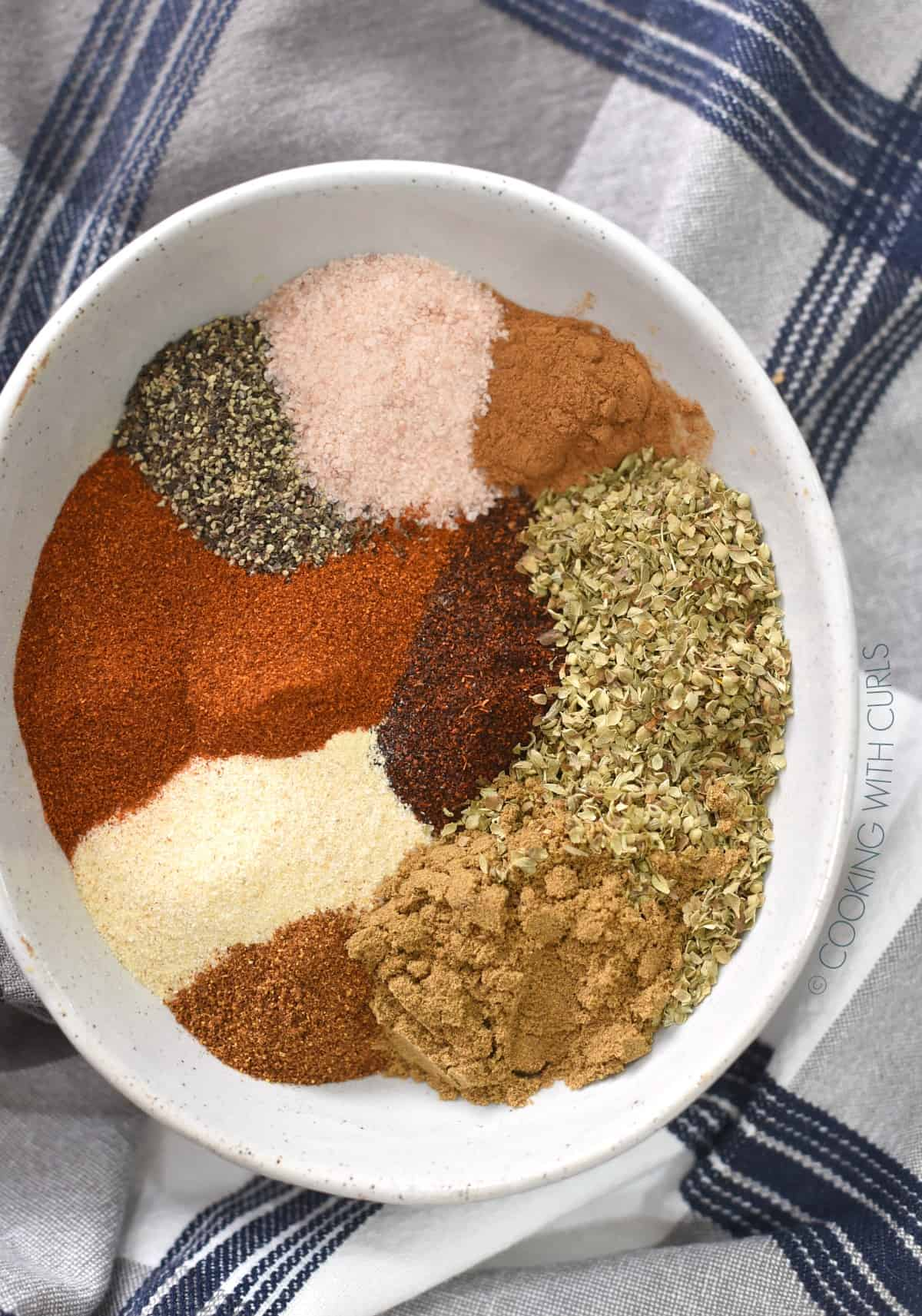 Looking down on a bowl with piles of seasonings.