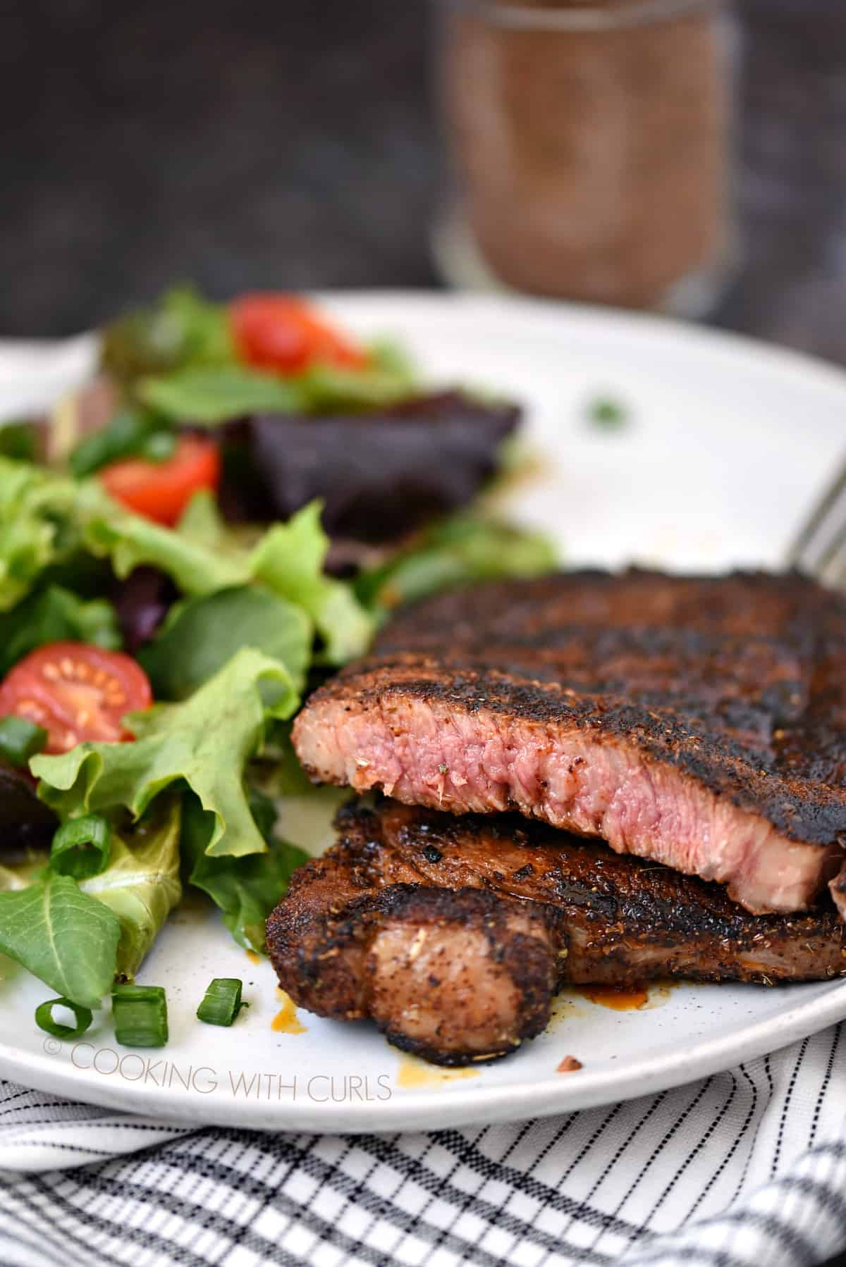 Cowboy Seasoning Rub on a perfectly grilled steak sitting next to a salad on a large white plate.