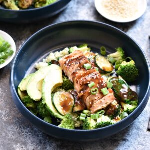 teriyaki glazed salmon and avocado slices top zucchini and broccoli in a blue bowl.
