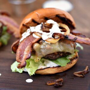 Grilled Double Bacon Burger with caramelized onions on a wood board.