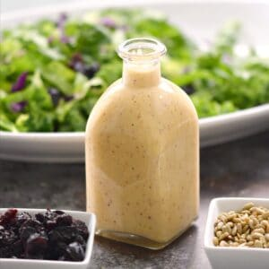 Sweet Onion and Citrus Dressing in a square, glass bottle with a bowl of salad in the background and square bowls of dried cherries and sunflower seeds in front.