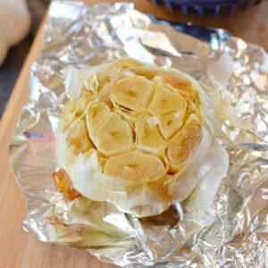 a roasted garlic bulb on a foil sitting on a wood cutting board.