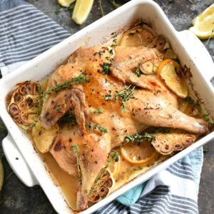 spatchcock chicken with garlic and lemon slices in a white baking dish.
