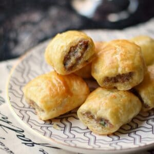 a pile of puff pastry sausage rolls on a gray and white patterned plate.
