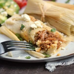 A close-up look at a pork tamale that has been cut into with a black fork, sitting next to a wrapped tamale.
