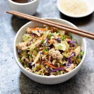 egg roll in a bowl with wood chopstick laying across the top and a bowl of sesame seeds in the right hand corner.
