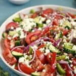 Tomato wedges, onion, bell pepper and cucumber slices tossed with a light vinaigrette and sprinkled with feta cheese on a large white serving platter with a bowl of feta in the background.