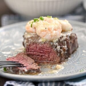 Shrimp Scampi topped Filet Mignon cut into on a gray plate