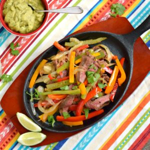 steak, onion and pepper slices cooked in an oval skillet with a bowl of guacamole on the side.