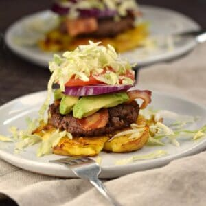 a smashed Yukon gold potato topped with a burger patty, bacon, avocado, onion and tomato slices with shredded lettuce on top.