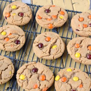 peanut butter cookies with reeses pieces on a wire cooling rack.