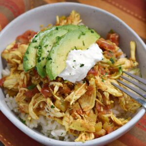 adobo spiced shredded chicken on white rice topped with avocado slices and sour cream.