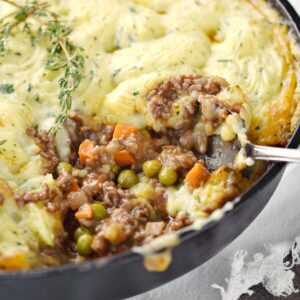 a close-up look at shepherd's pie in a skillet with a big scoop taken out of the lower right corner.