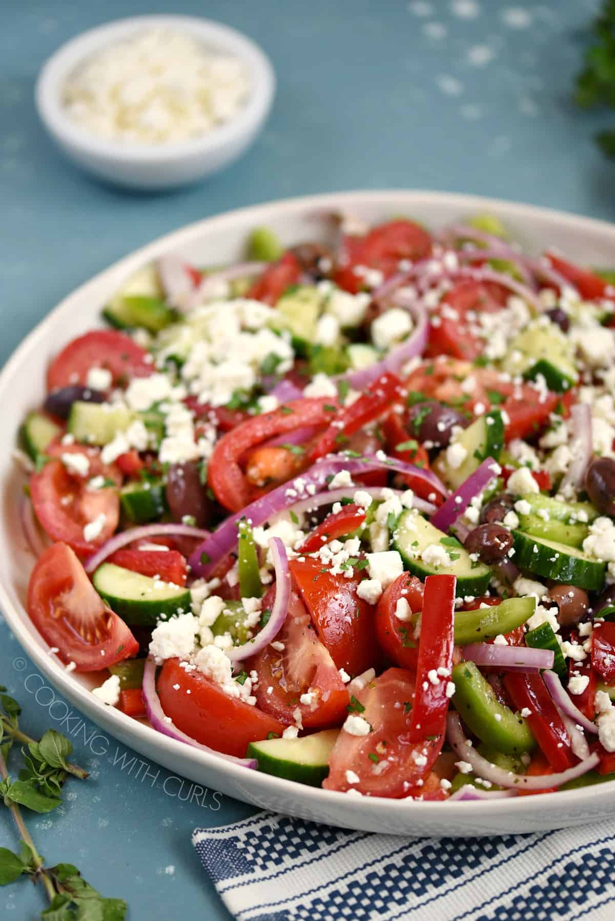 A Big Greek Salad consisting of tomatoes, cucumbers, bell pepper, onions, olives and feta cheese on a white serving platter.