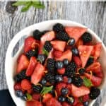 Looking down on a white serving bowl filled with watermelon wedges, blackberries, strawberries and blueberries with title across the top of the image.