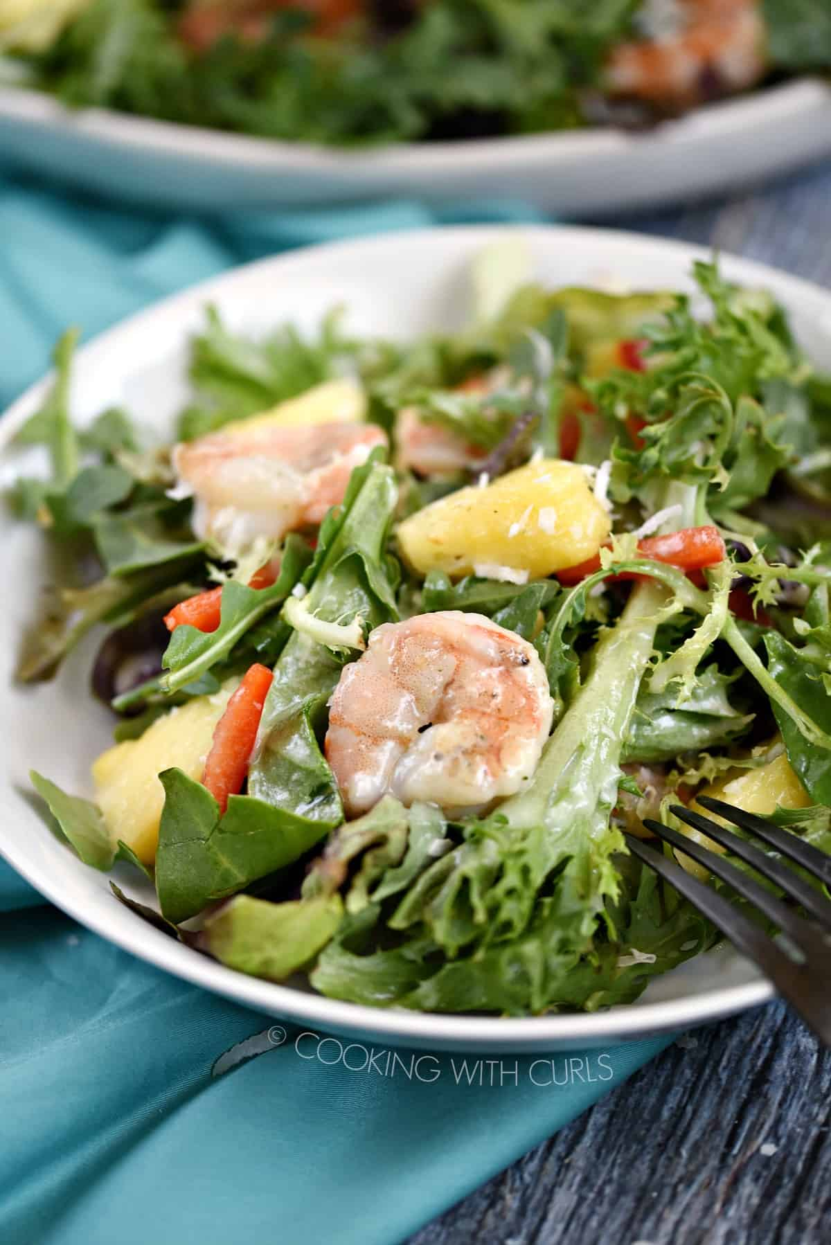 A close up image of a white bowl filled with salad greens, pineapple chunks, pepper strips and grilled shrimp drizzled with pina colada vinaigrette.