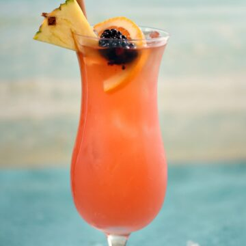 a pink cocktail in an ice filled hurricane glass garnished with a pineapple wedge, orange slice, blackberry and bamboo straw with an ocean image in the background.