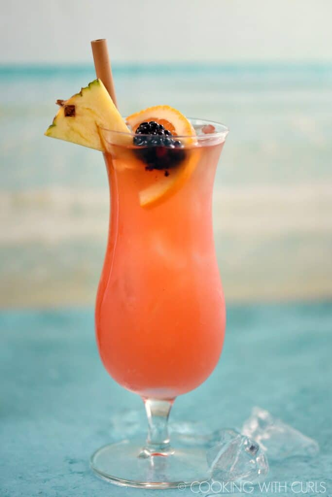an ice filled hurricane glass with a pink cocktail that is garnished with a pineapple wedge, orange slice, blackberry and bamboo straw.