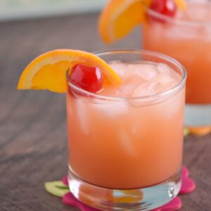 A small glass of Caribbean Rum Punch garnished with a cherry and orange wheel with a second cocktail in the background.