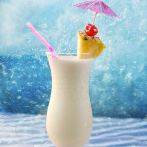 a tropical pina colada in a hurricane glass garnished with a pineapple wedge, cherry and purple umbrella.
