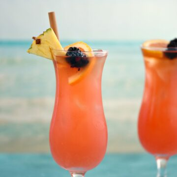 two hurricane glasses filled with a pink cocktail and garnished with a straw, pineapple wedge, orange slice and blackberry with an ocean image in the background.