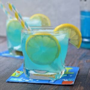 two blue lemonade cocktails garnished with lemon and striped straws.