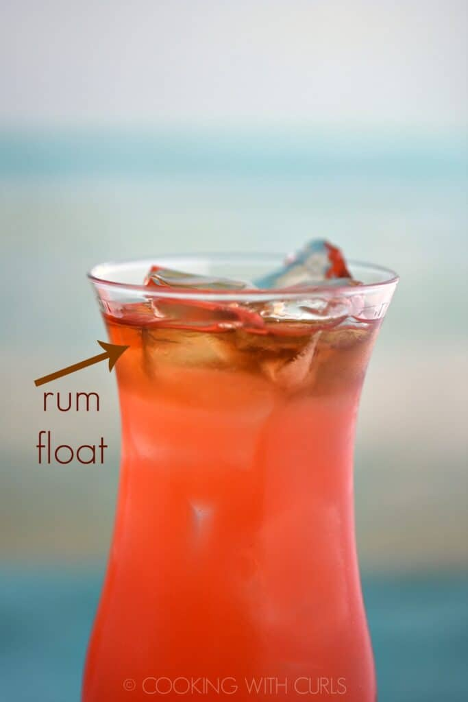 close up of pink cocktail with a dark rum float on top of the ice cubes.