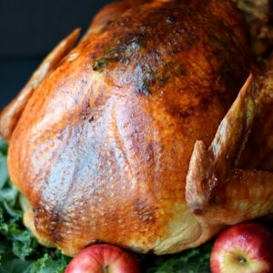 close-up of a whole roasted turkey sitting on a bed of greens with whole apples around the bottom.