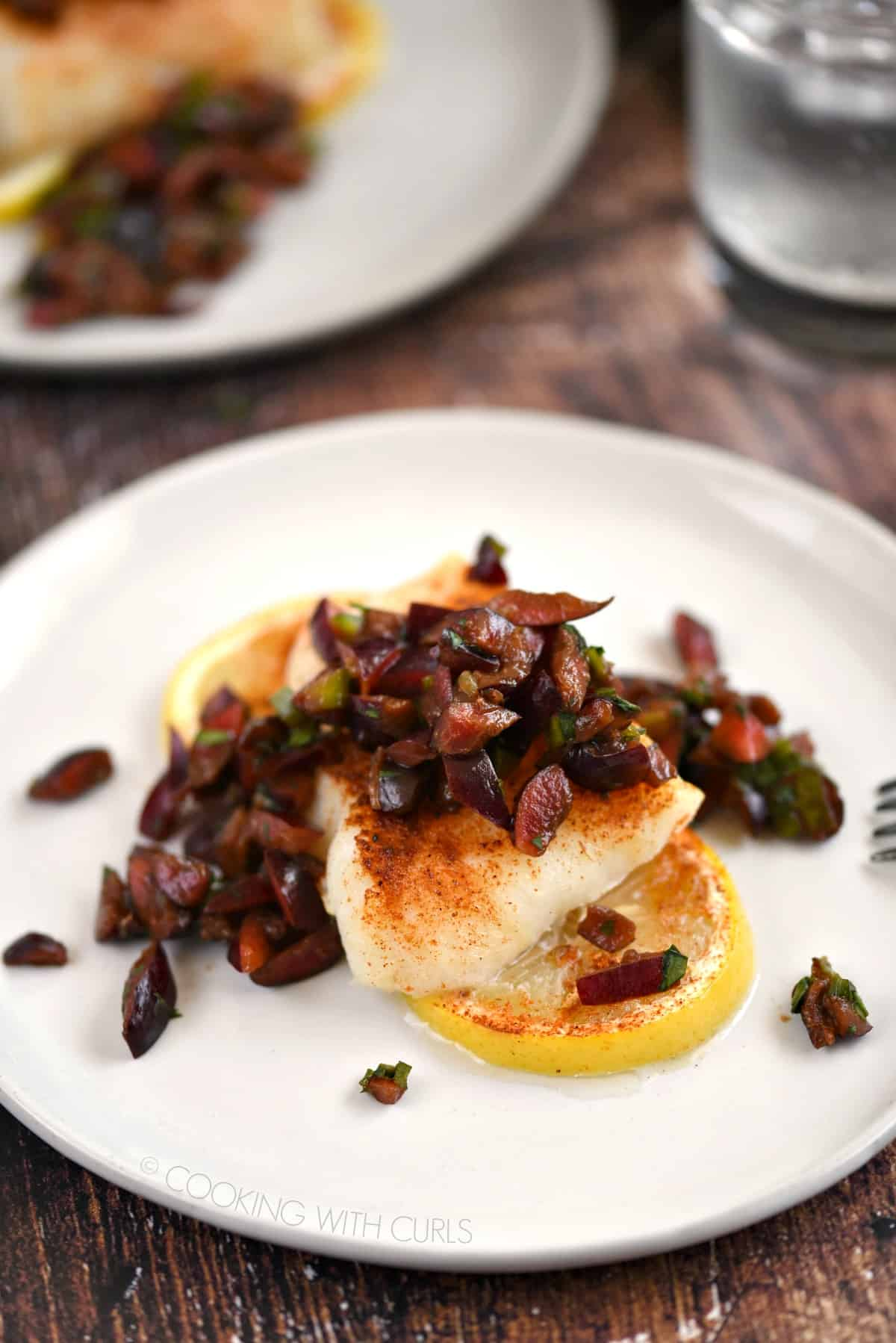 two white plates with lemon slices topped with baked cod and cherry salsa.