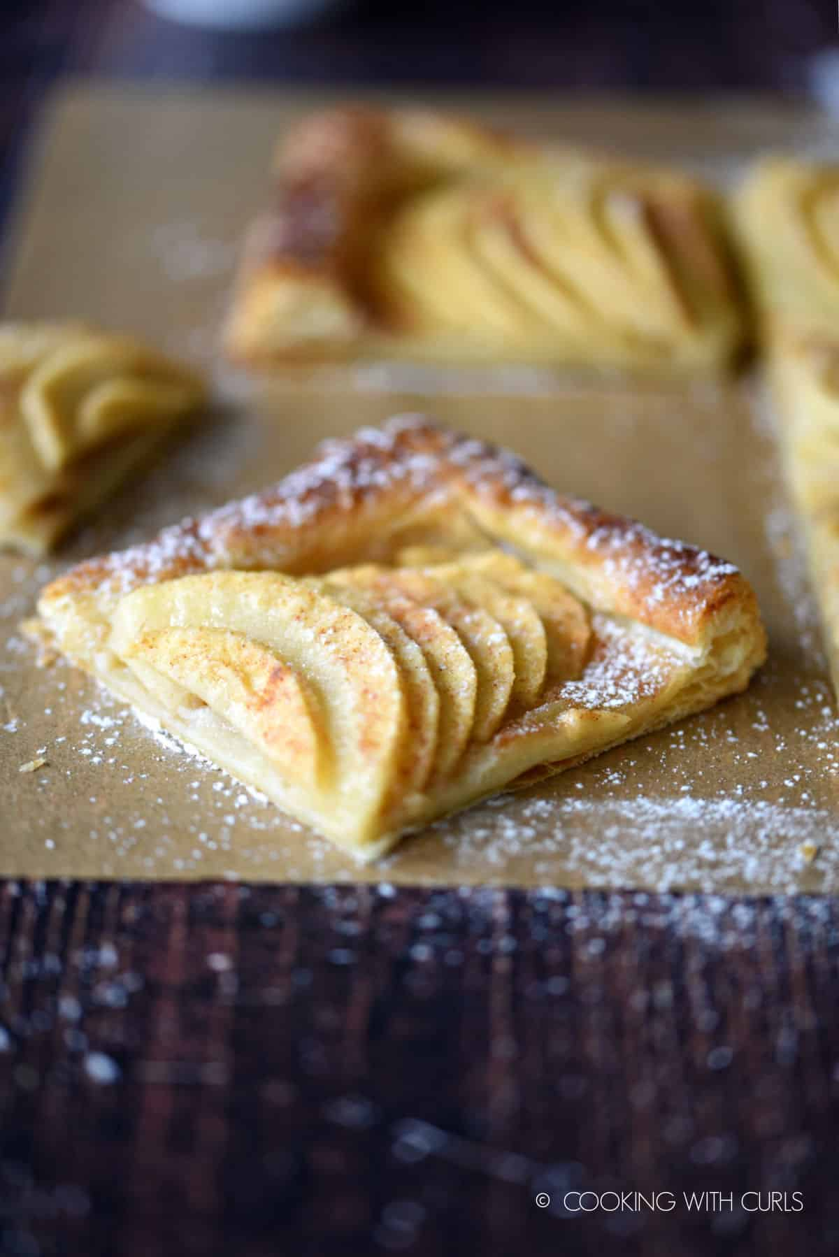 a corner piece of puff pastry apple tart pulled away from the remaining pieces on a sheet of parchment paper, and dusted with powdered sugar.