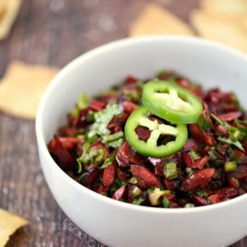 chopped cherries, jalapeno, and cilantro salsa in a white bowl topped with two jalapeno slices with pita chips scattered around the table.