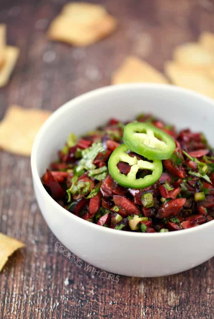 a white bowl filled with chopped cherries, jalapeno and cilantro topped with two jalapeno slices with pita chips scattered around the table.