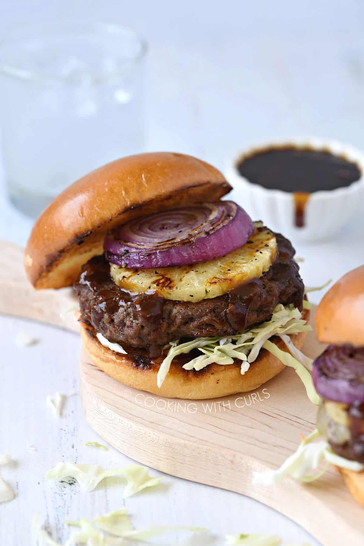 a grilled Hawaiian teriyaki burger with the top bun tilted at an angle with a bowl of sauce in the background and the edge of a second burger in front.