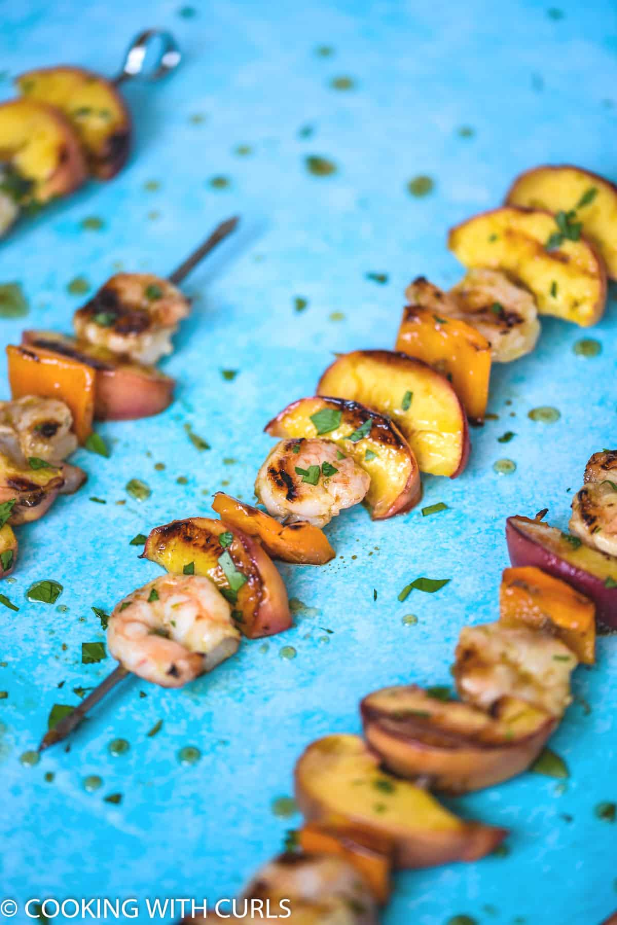 close up image of a metal skewer filled with grilled shrimp, peach wedges, and orange bell pepper squares with three more skewers in the background.