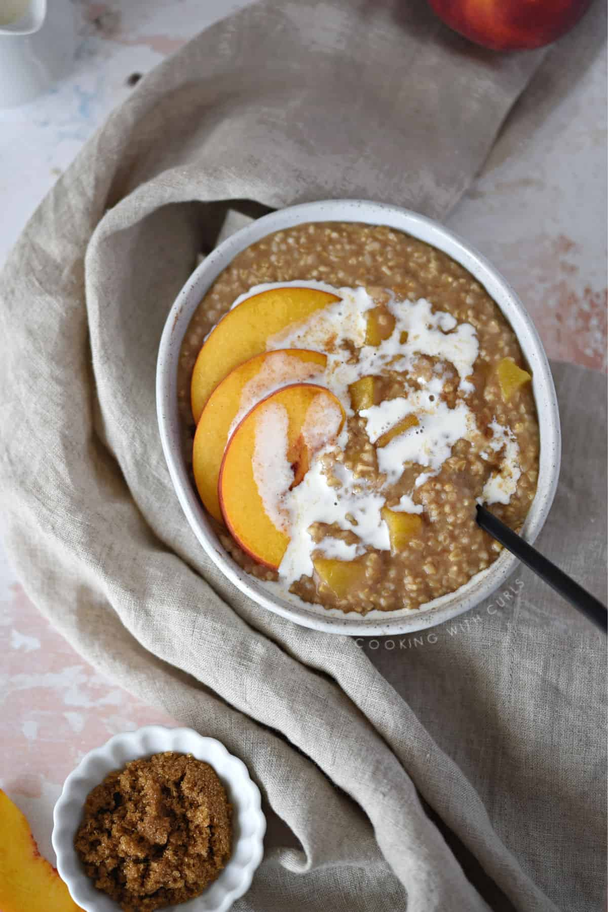 looking down on a bowl of steel cut oats topped with peach slices and cream, with a small bowl of brown sugar in the bottom left corner and the edge of a full peach in the upper right corner.
