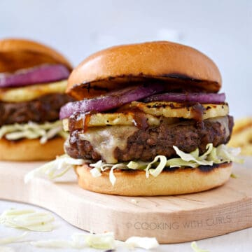 a wood cutting board with a big cheeseburger topped with grilled pineapple and red onion slices, shredded cabbage and teriyaki sauce on a brioche bun with a second burger in the background.
