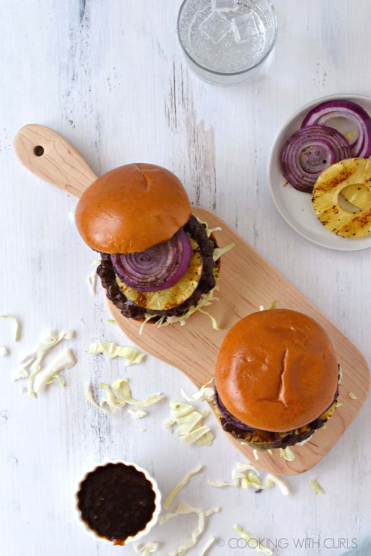 looking down on two burgers topped with grilled buns sitting on a wood cutting board with a small bowl of teriyaki sauce in front, and plate with grilled pineapple and red onion rings and a glass of bubbly water in the background.