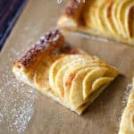 a slice of puff pastry apple tart at an angle on parchment paper dusted with powdered sugar.