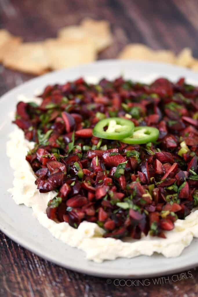 chopped cherries,jalapeno and cilantro salsa spread over cream cheese on a large plate
