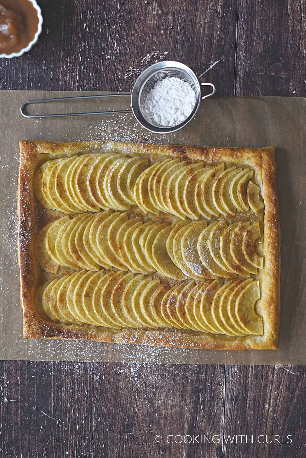 looking down on rows of apple slices on a puff pastry crust on a sheet of parchment paper with powdered sugar in a metal sifter at the top.