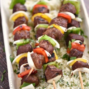 four wooden skewers with grilled steak cubes, onion slices and bell pepper squares laying on a bed of cilantro lime rice.